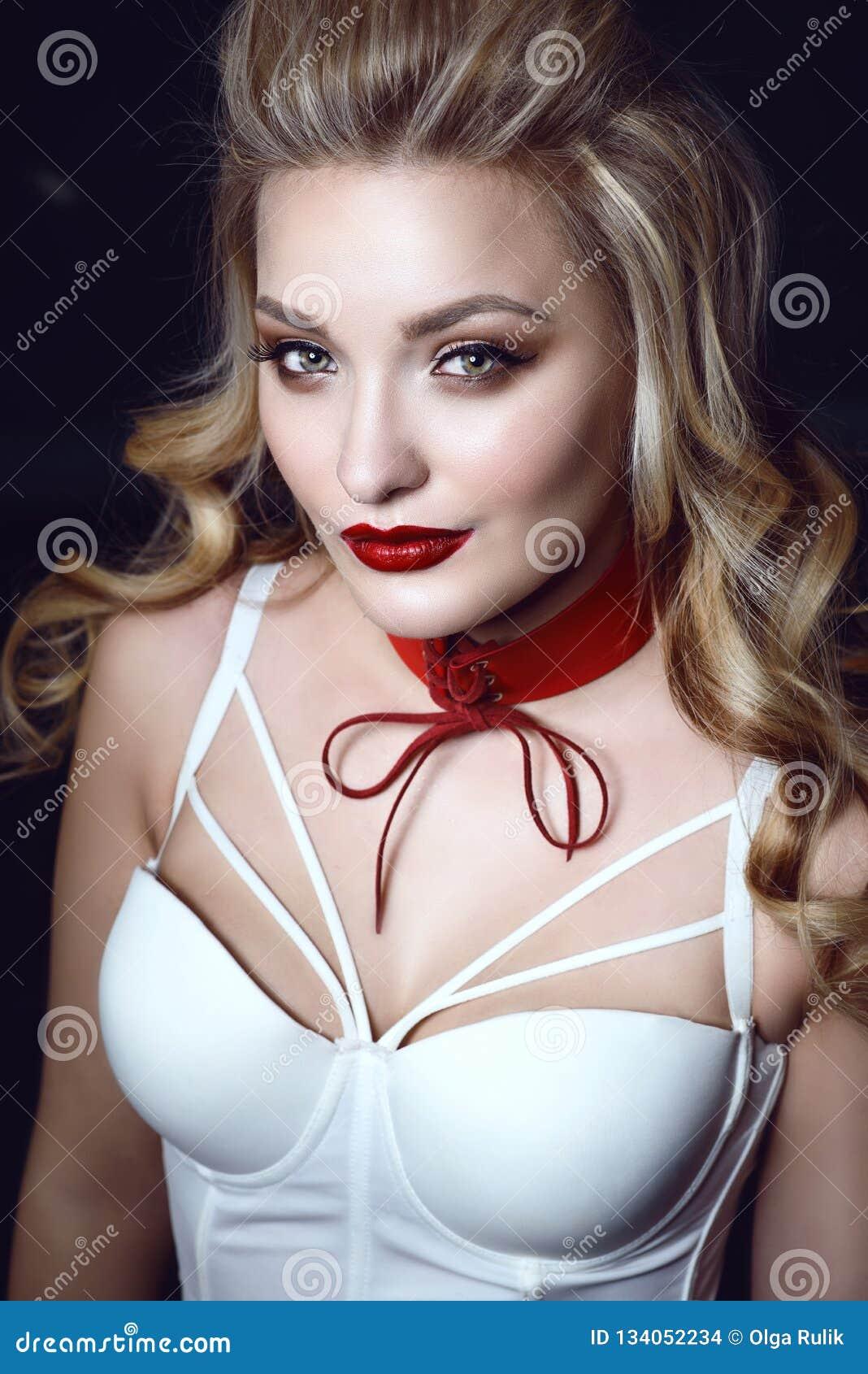 与完善的美好的微笑的白肤金发的模型组成并且废弃了头发佩带的白色束腰束缚顶面和红色窒息物