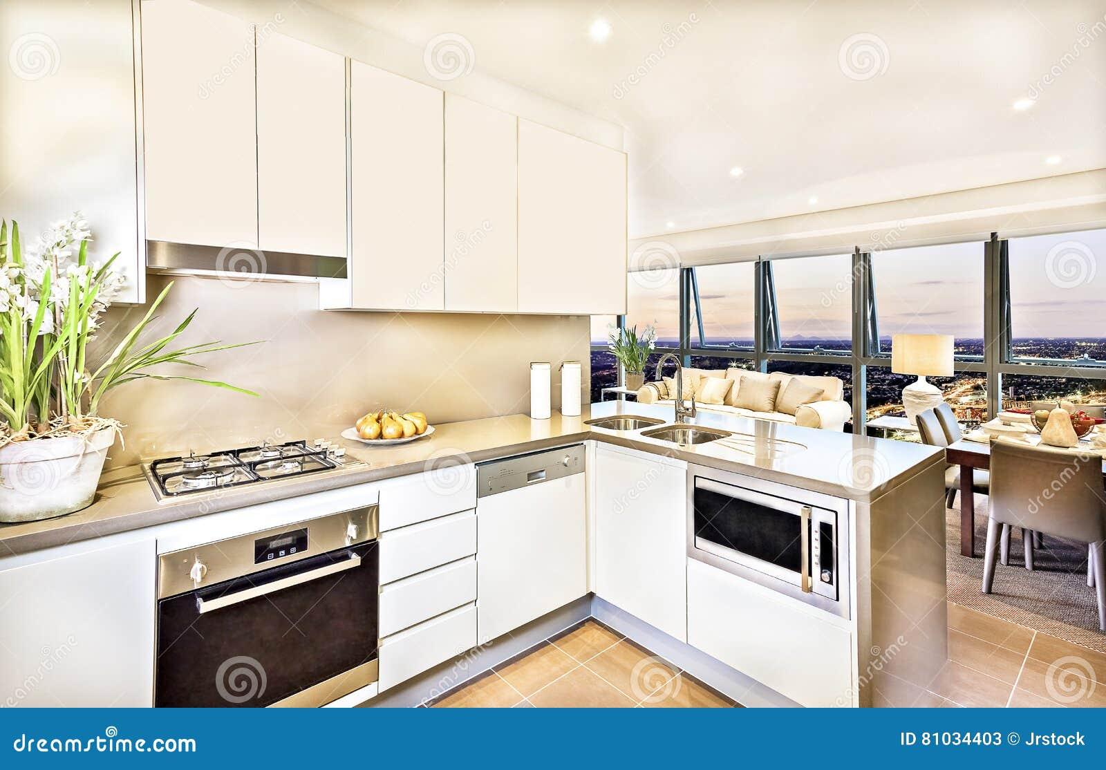 与客厅区域的现代厨房内部晚上