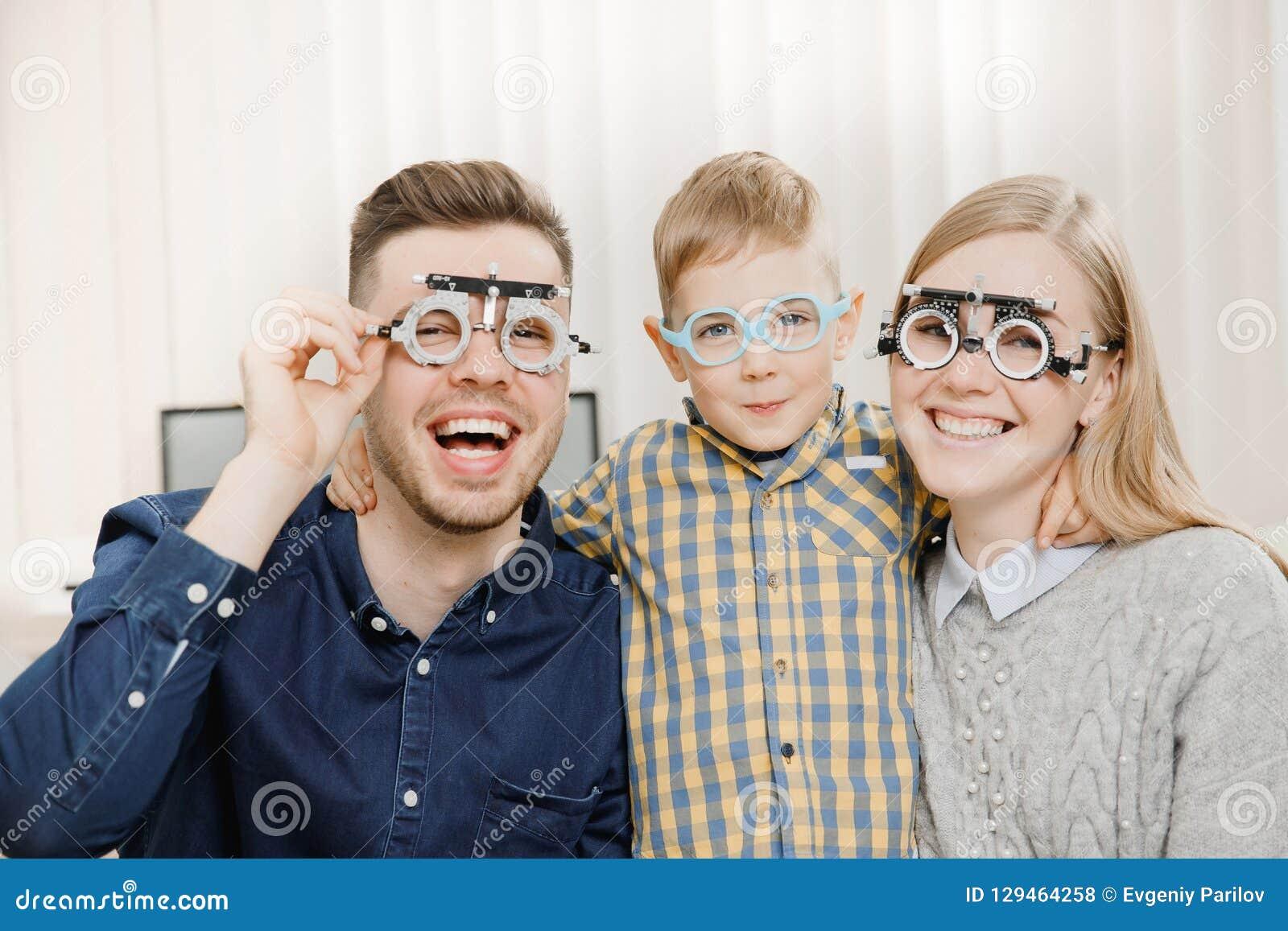 与小儿童招待会医生眼科医生的快乐的家庭使用玻璃