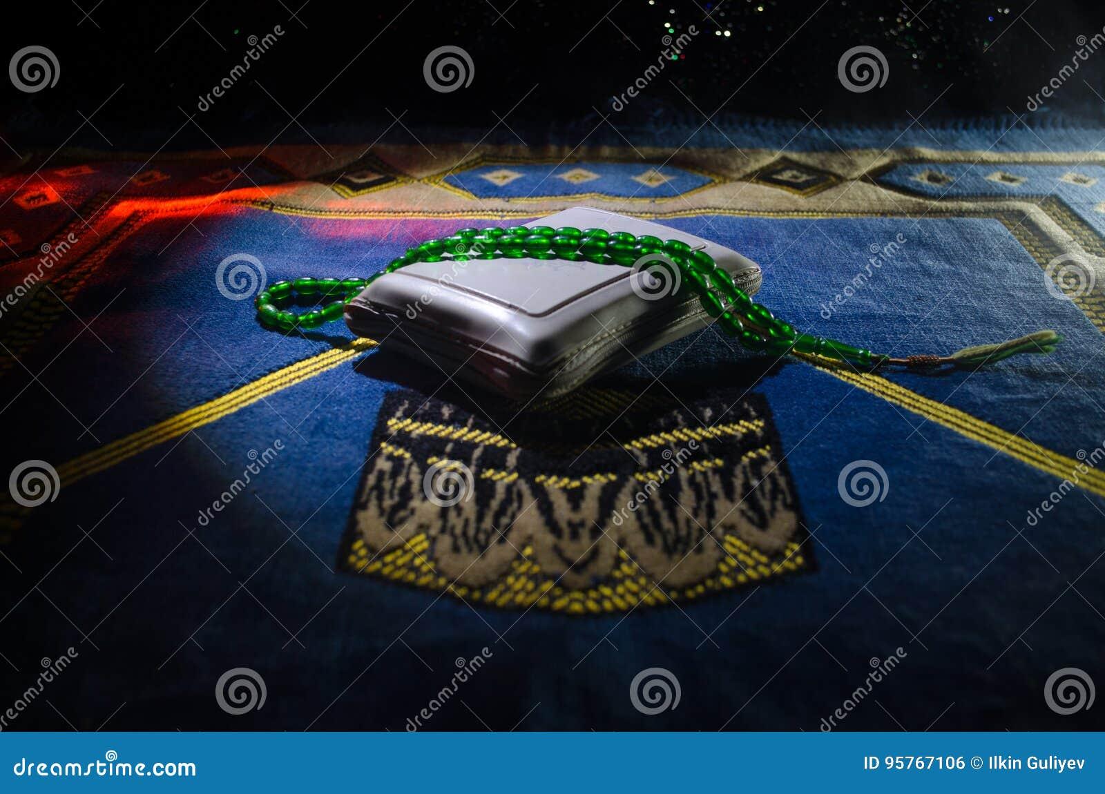 与小珠在跪垫,穆斯林Tasbih的圣洁古兰经是与一起由穆斯林传统上使用念珠的串