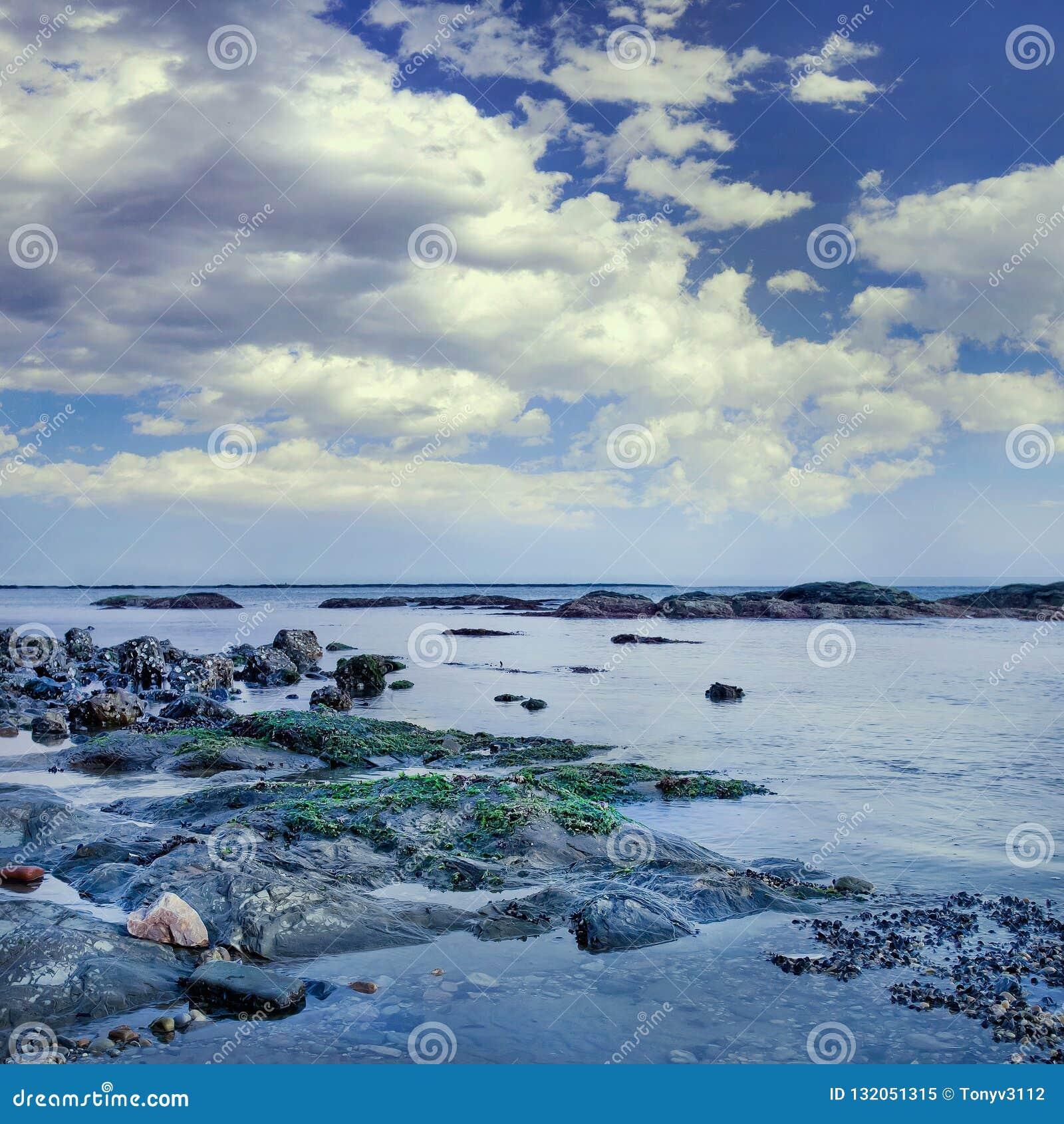 与岩石和剧烈的云彩,大连,中国的海滨