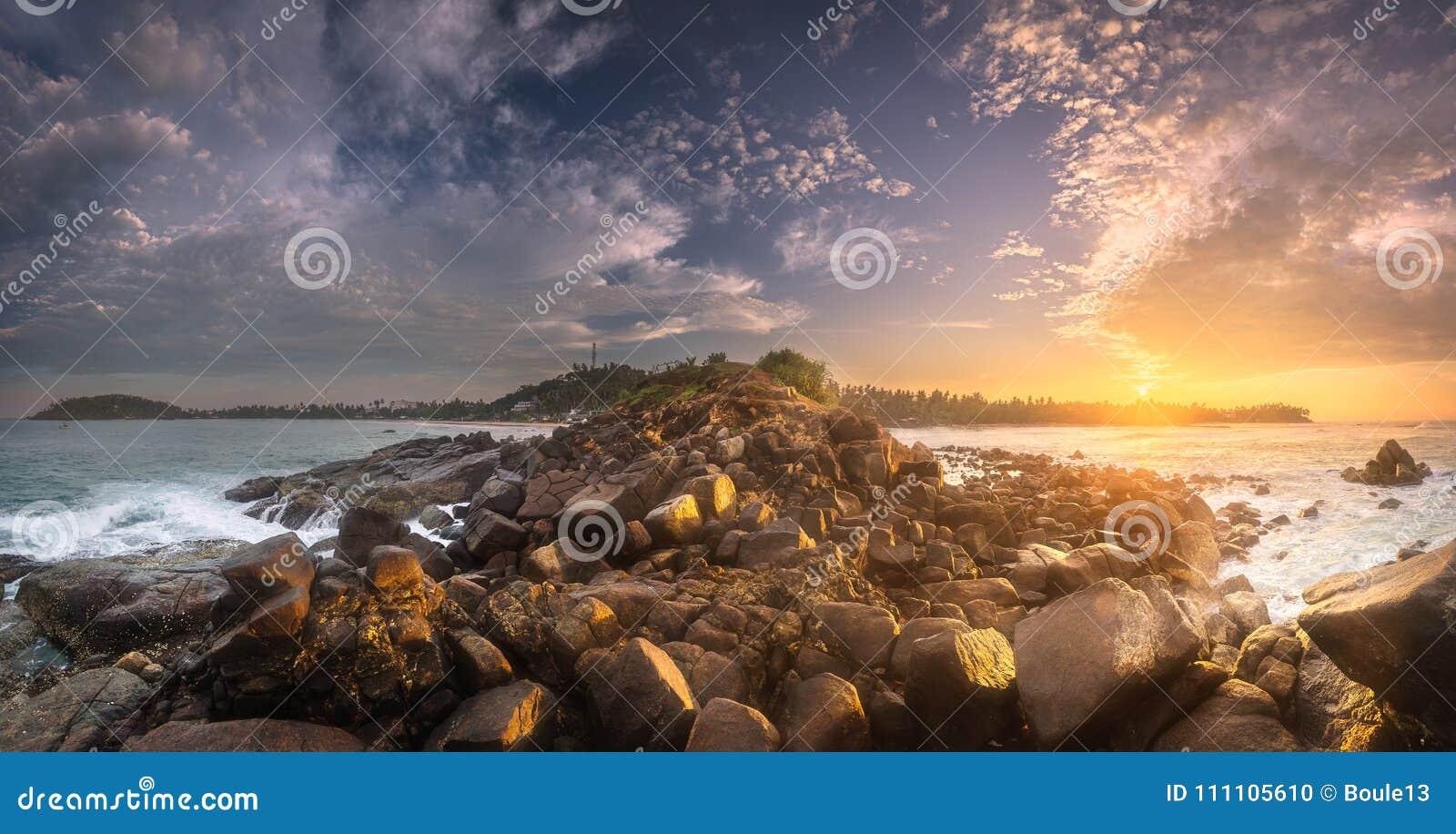与岩石的热带海滩在海洋沙子海岸