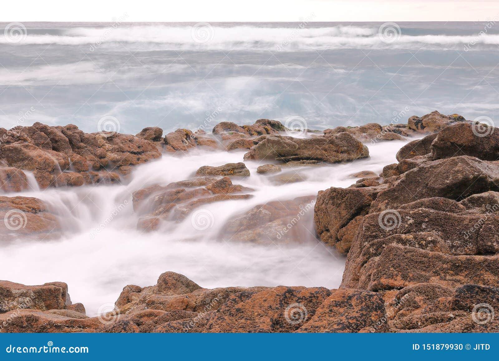 与岩石的长的曝光摄影在与海的海岸有波浪的在夏天