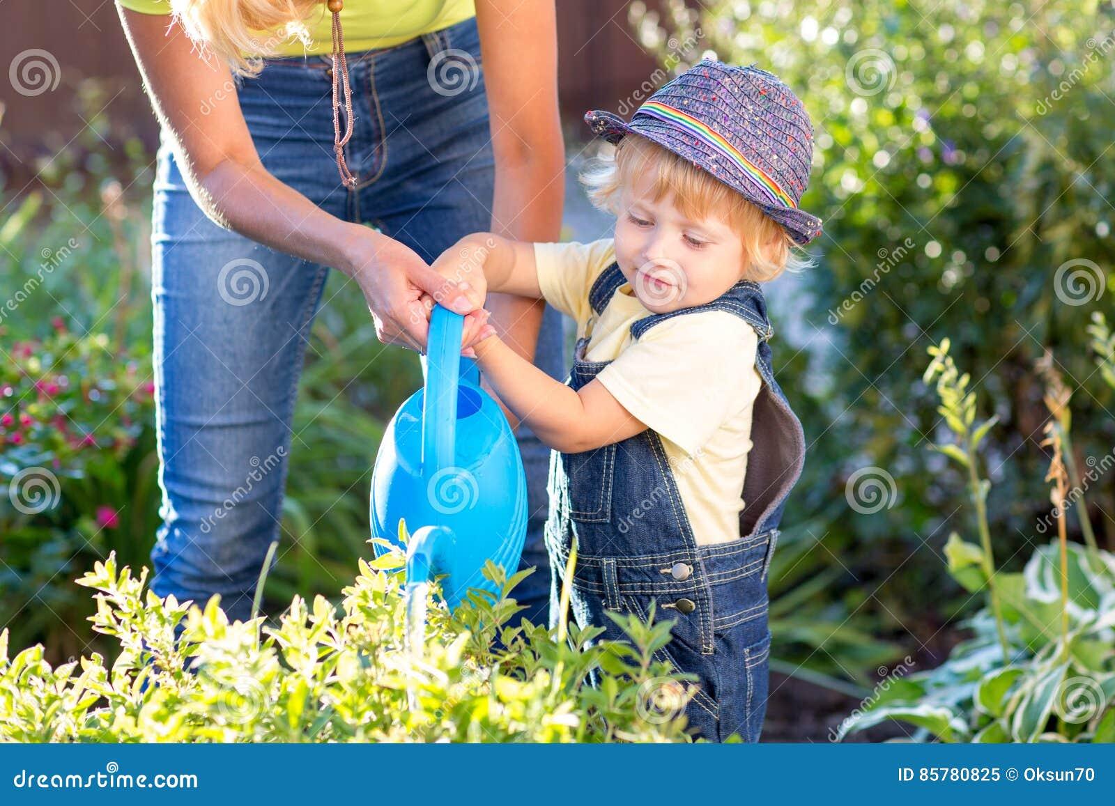 与工作在庭院里的妈妈的孩子 儿童浇灌的花 母亲帮助小儿子