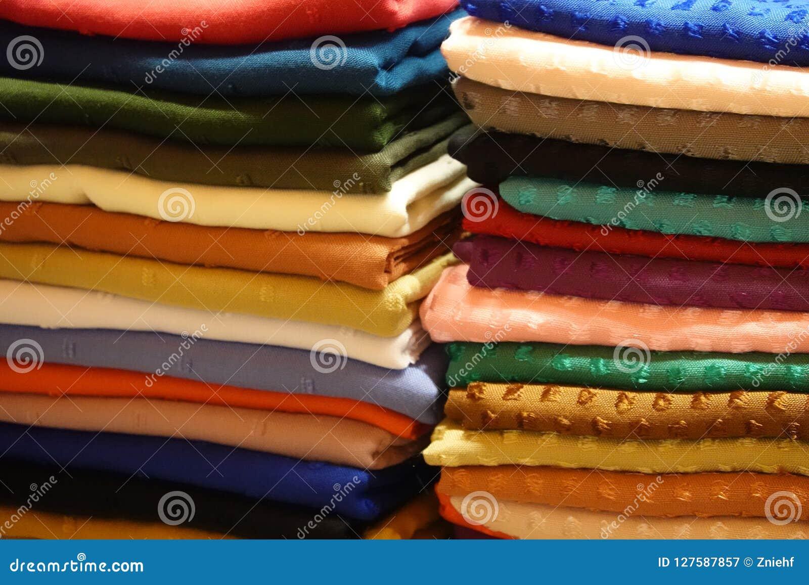 与布料的在许多不同的颜色的堆和织品在一个st