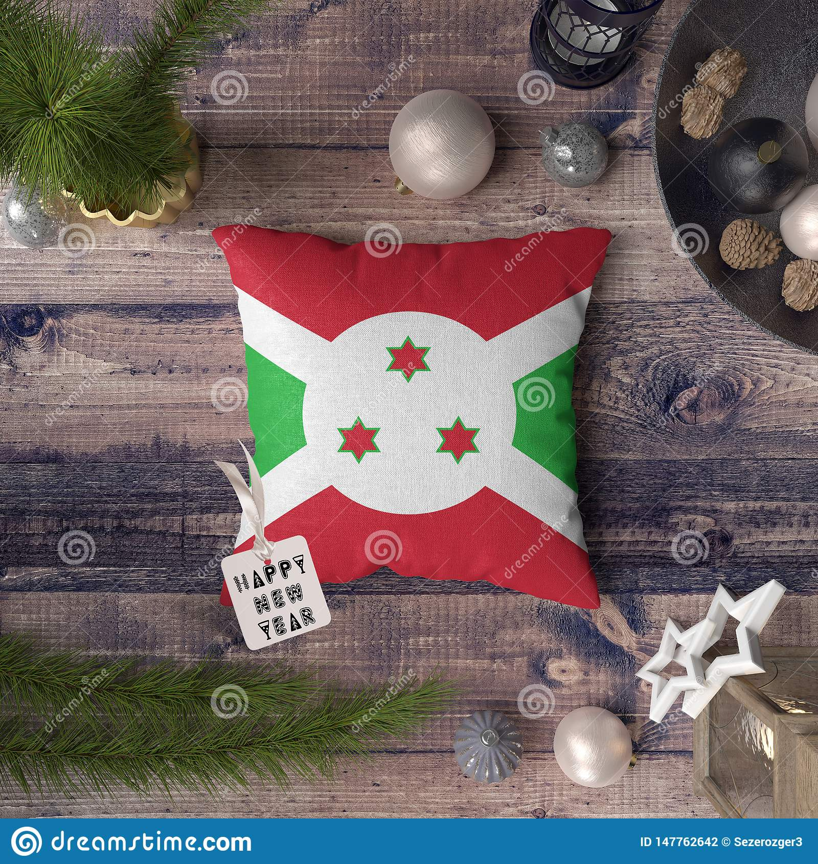 与布隆迪旗子的新年快乐标记在枕头 在木桌上的圣诞装饰概念与可爱的对象