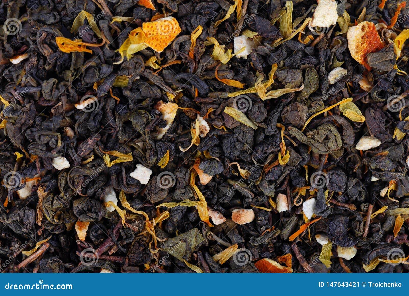 与干燥花和糖煮的橙色背景的绿色锡兰茶
