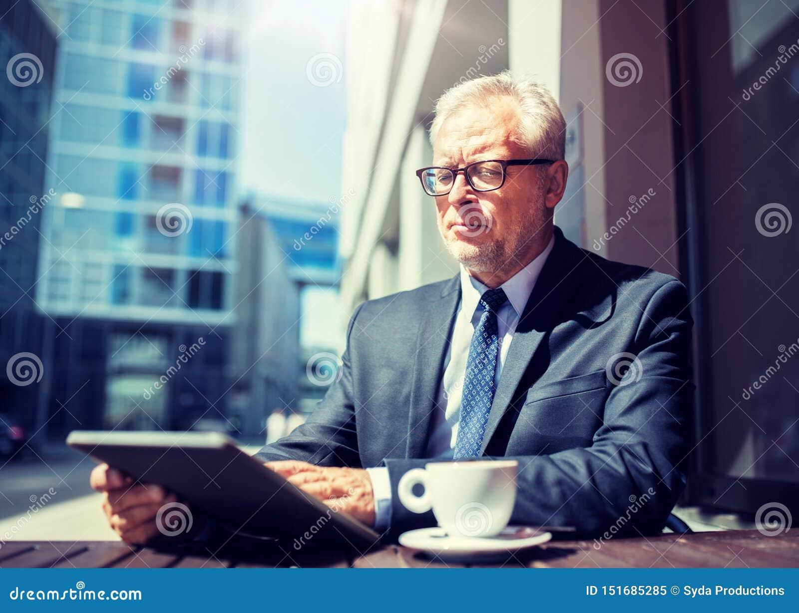 与平板电脑的资深商人喝咖啡的