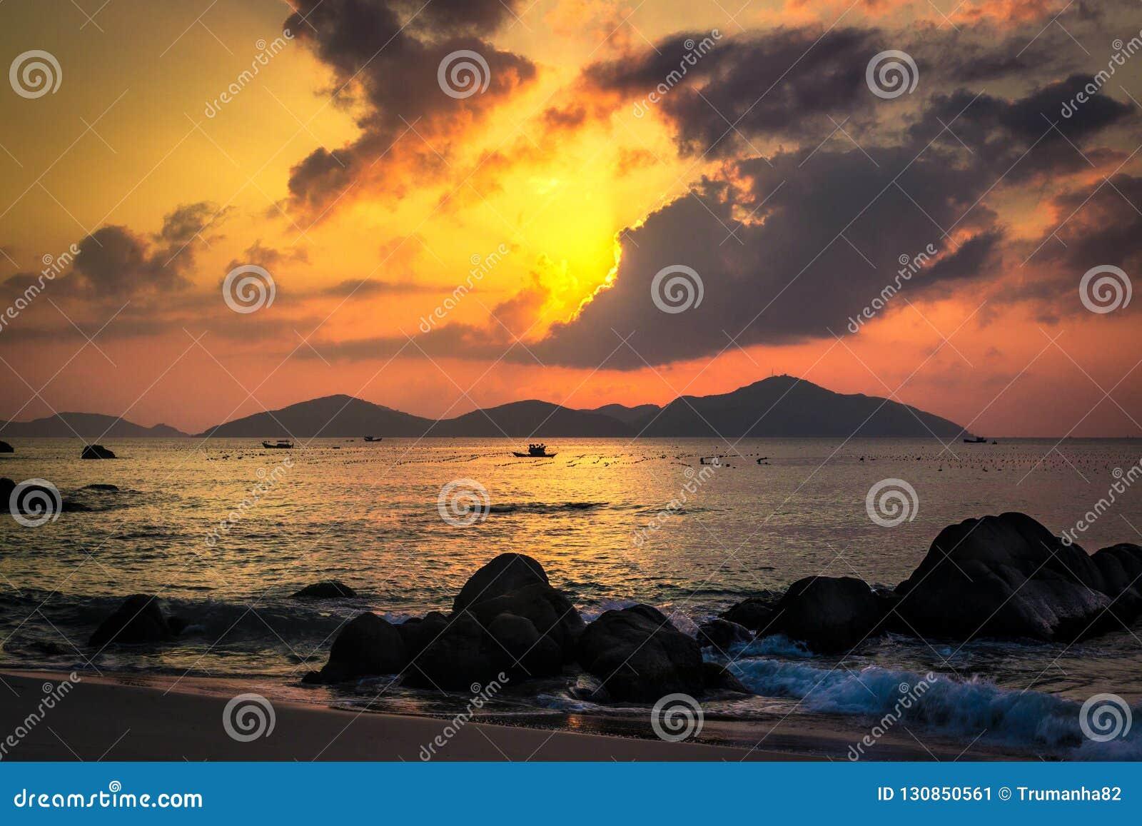 与平静的海滩、冰砾、海岛、乌云和暗藏的太阳的自然海景在日出
