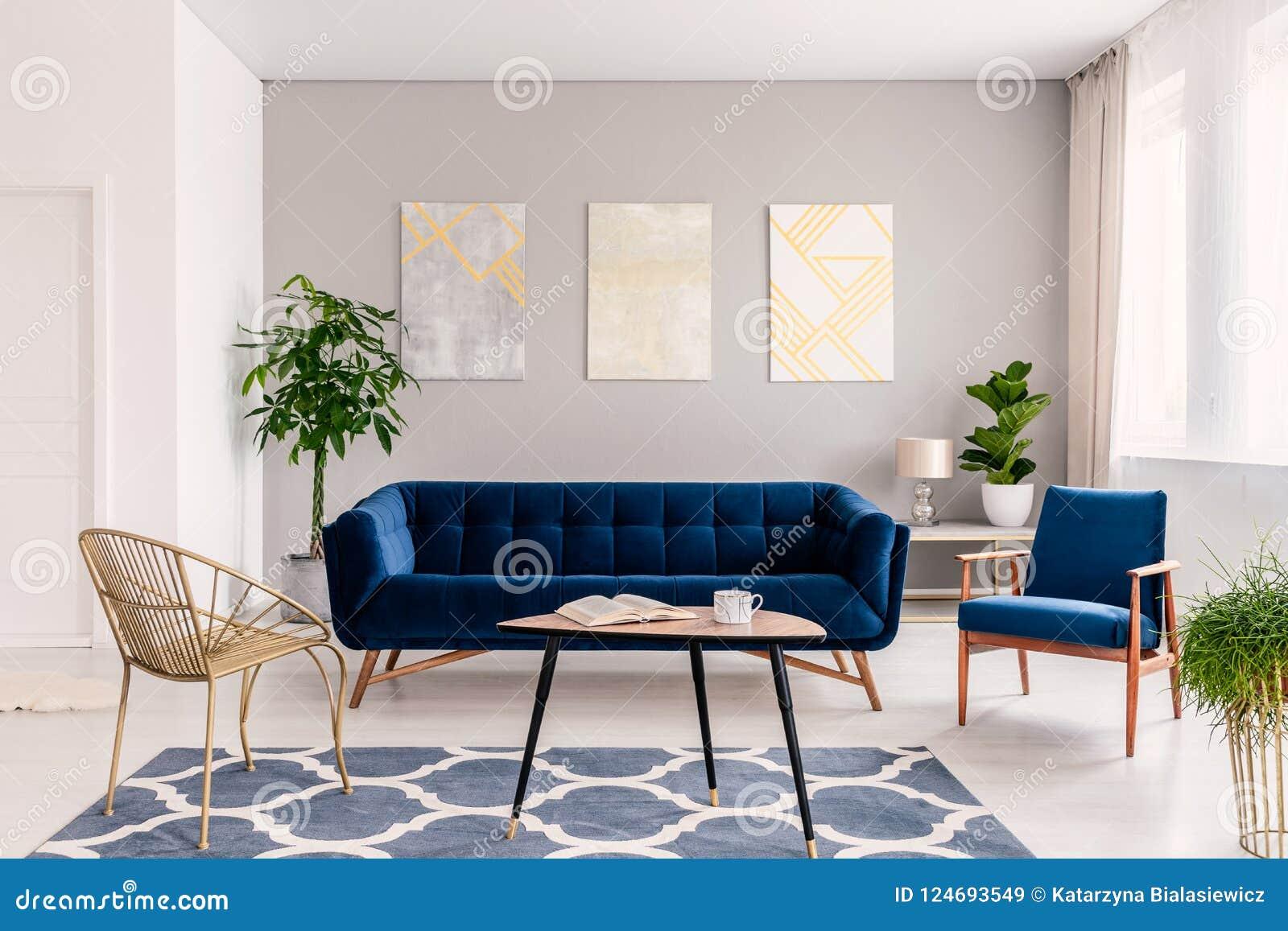 与开放书的咖啡桌和茶抢劫在地毯的身分在明亮的客厅内部,金子c真正的照片与新鲜的植物的