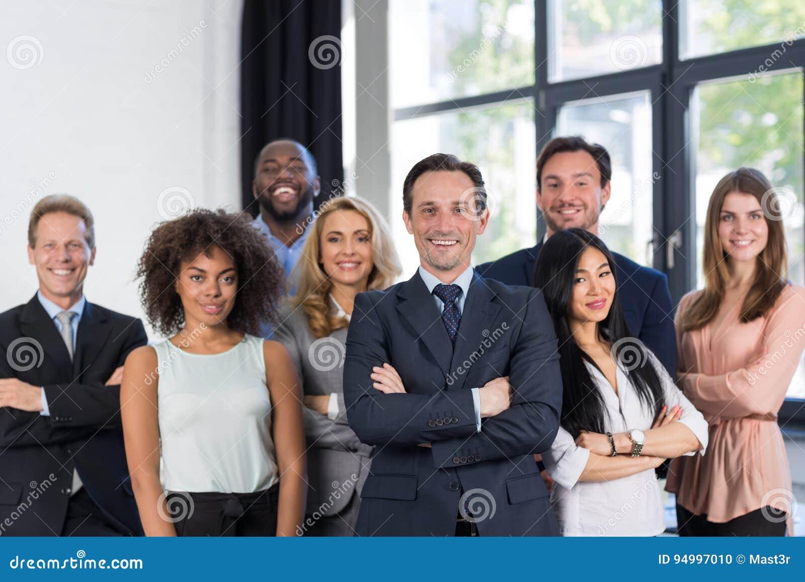 与成熟领导人的上司和商人小组在前景在办公室,领导概念,成功的混合种族队