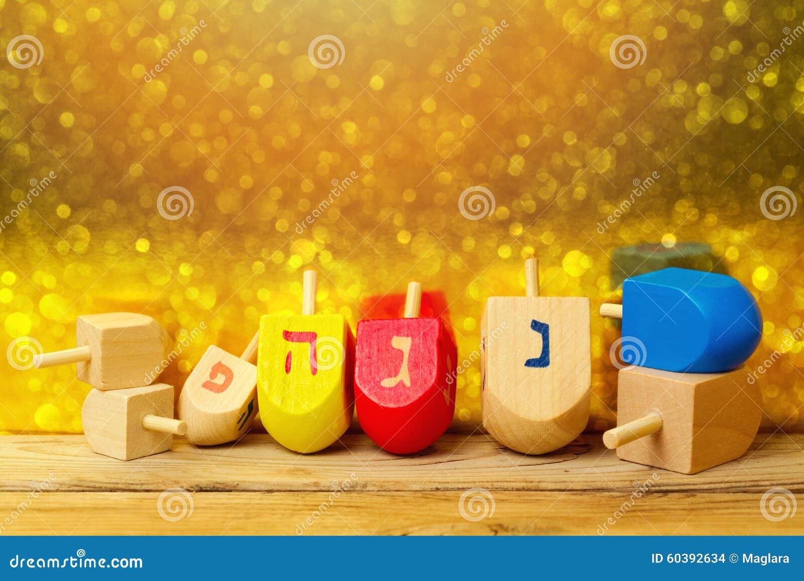 与抽陀螺dreidel的犹太假日光明节背景在金黄bokeh的木桌上