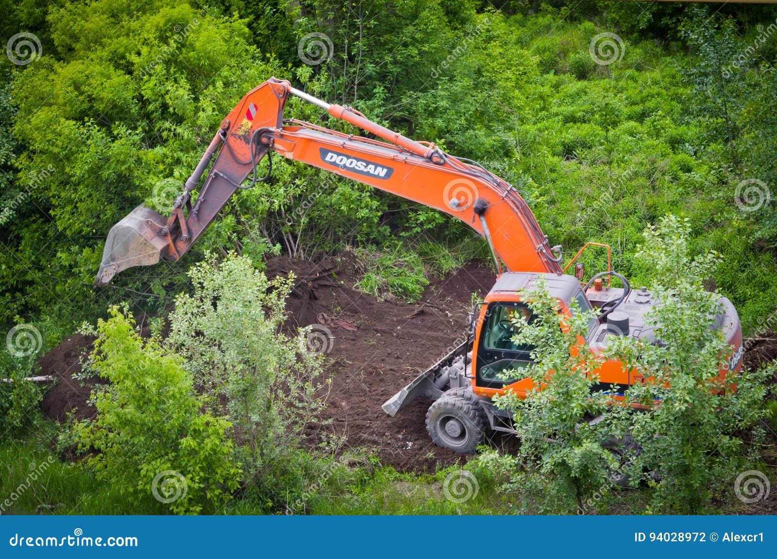 与挖掘机的清洁草丛