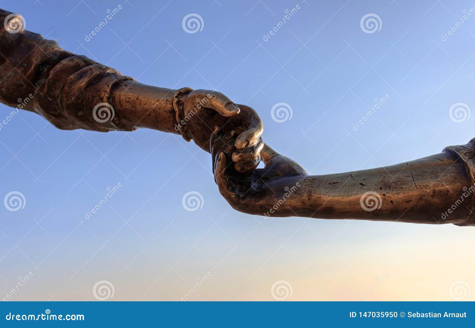 与握她的手的男孩和女孩的雕象