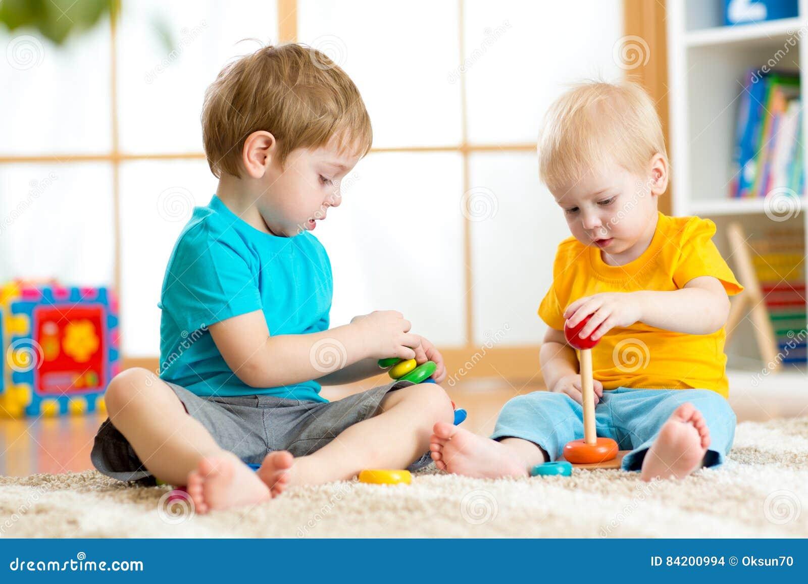与教育玩具的儿童游戏在幼儿园或幼儿园 小孩孩子和婴孩在家修造金字塔玩具或