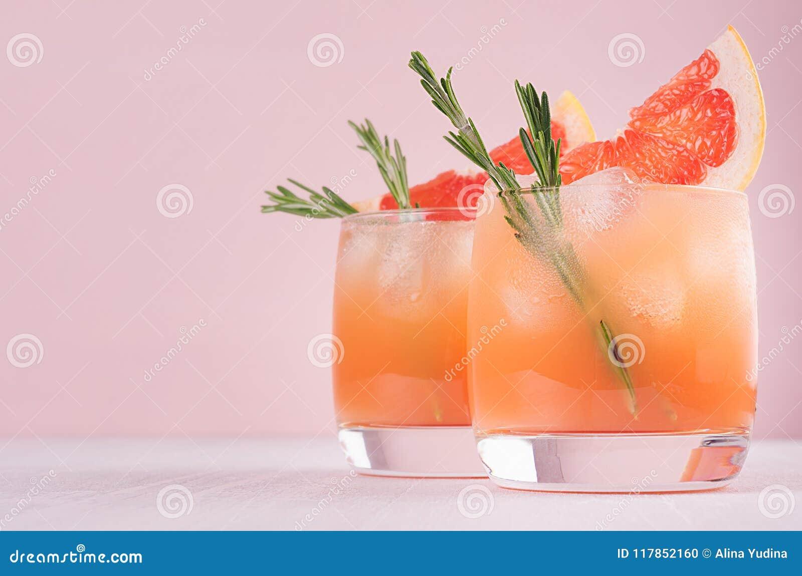 与新鲜的葡萄柚夏天酒精鸡尾酒,冰,在时尚桃红色背景的迷迭香的两高雅冷的湿水杯