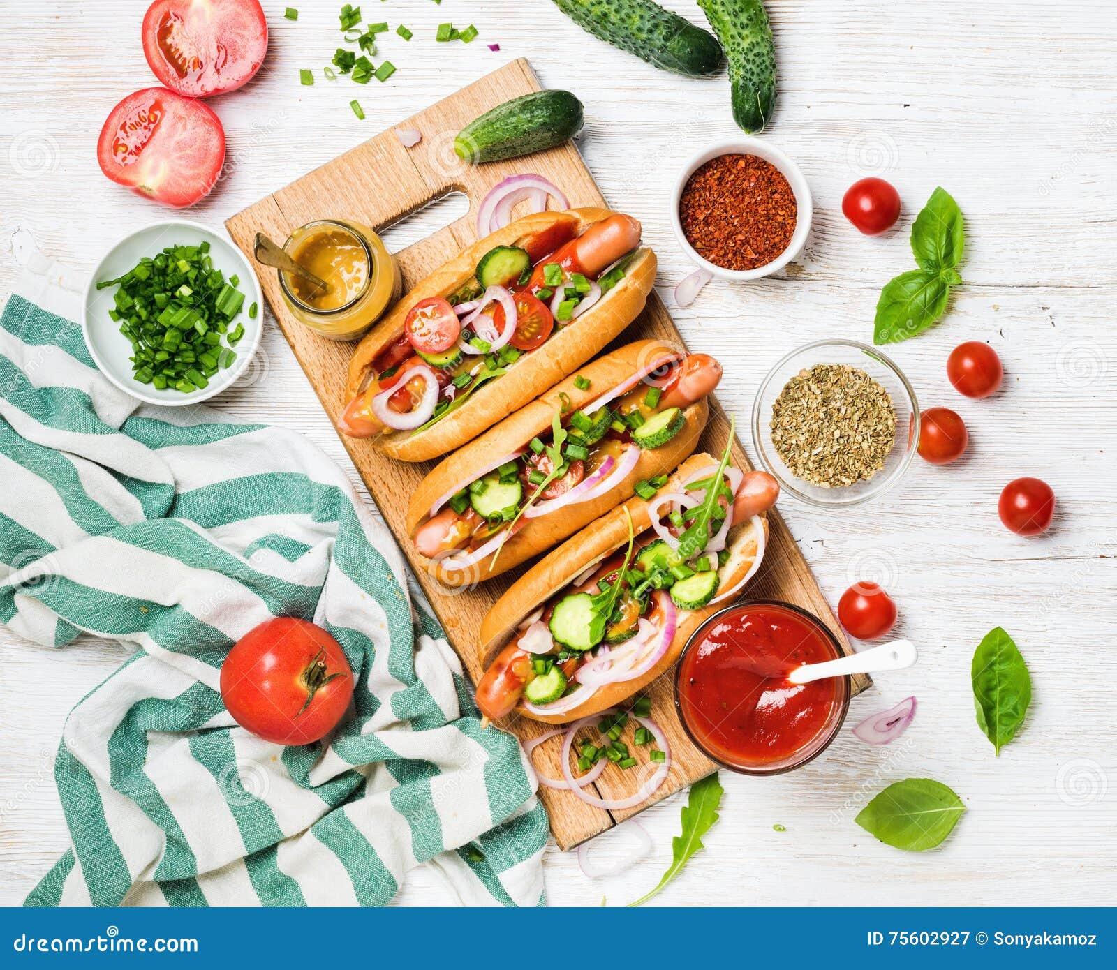 与新鲜蔬菜、香料、番茄酱和芥末的自创热狗