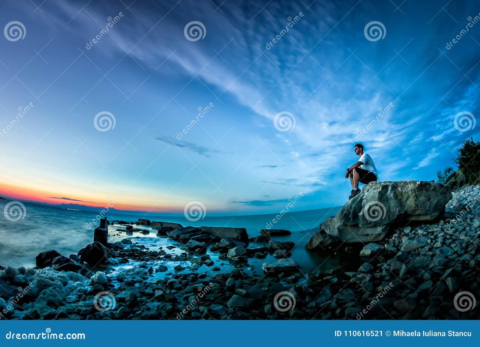 与日落的美好的风景在湖和一个年轻人坐岩石