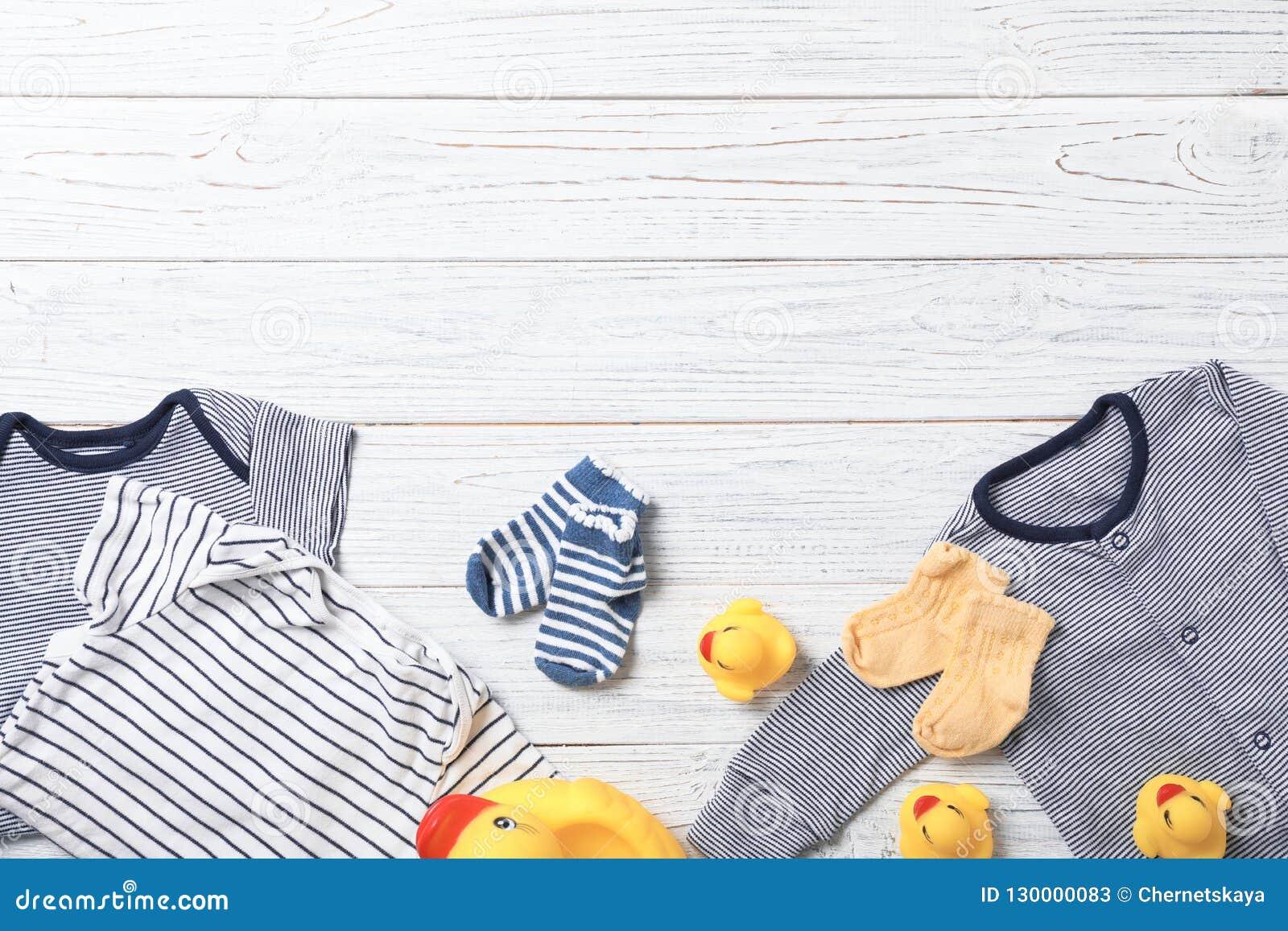 与时髦的婴孩衣裳和玩具的平的被放置的构成在木背景