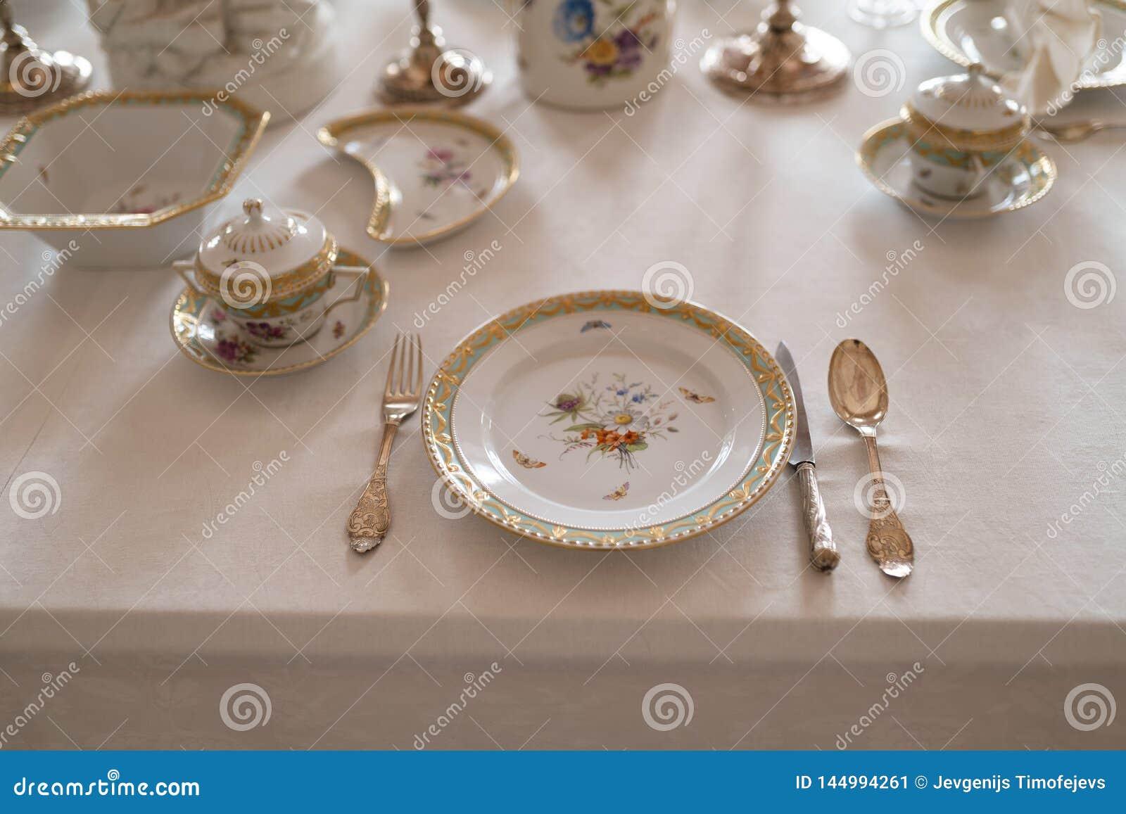 与昂贵的减速火箭的皇家雄伟瓷服务板材和利器的婚姻的桌装饰在宫殿