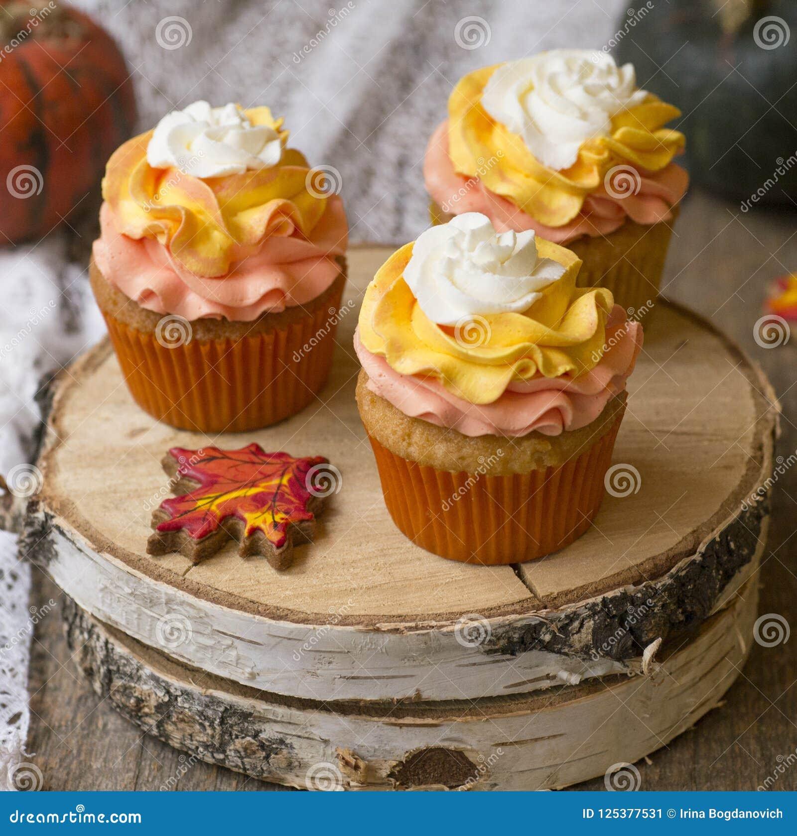 与明亮的橙色盖帽的南瓜杯形蛋糕