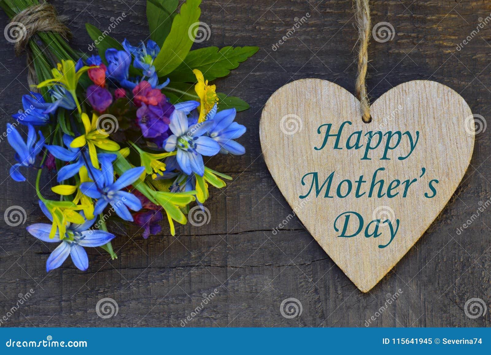 与春天的愉快的母亲` s天贺卡开花花束和装饰心脏在老木背景