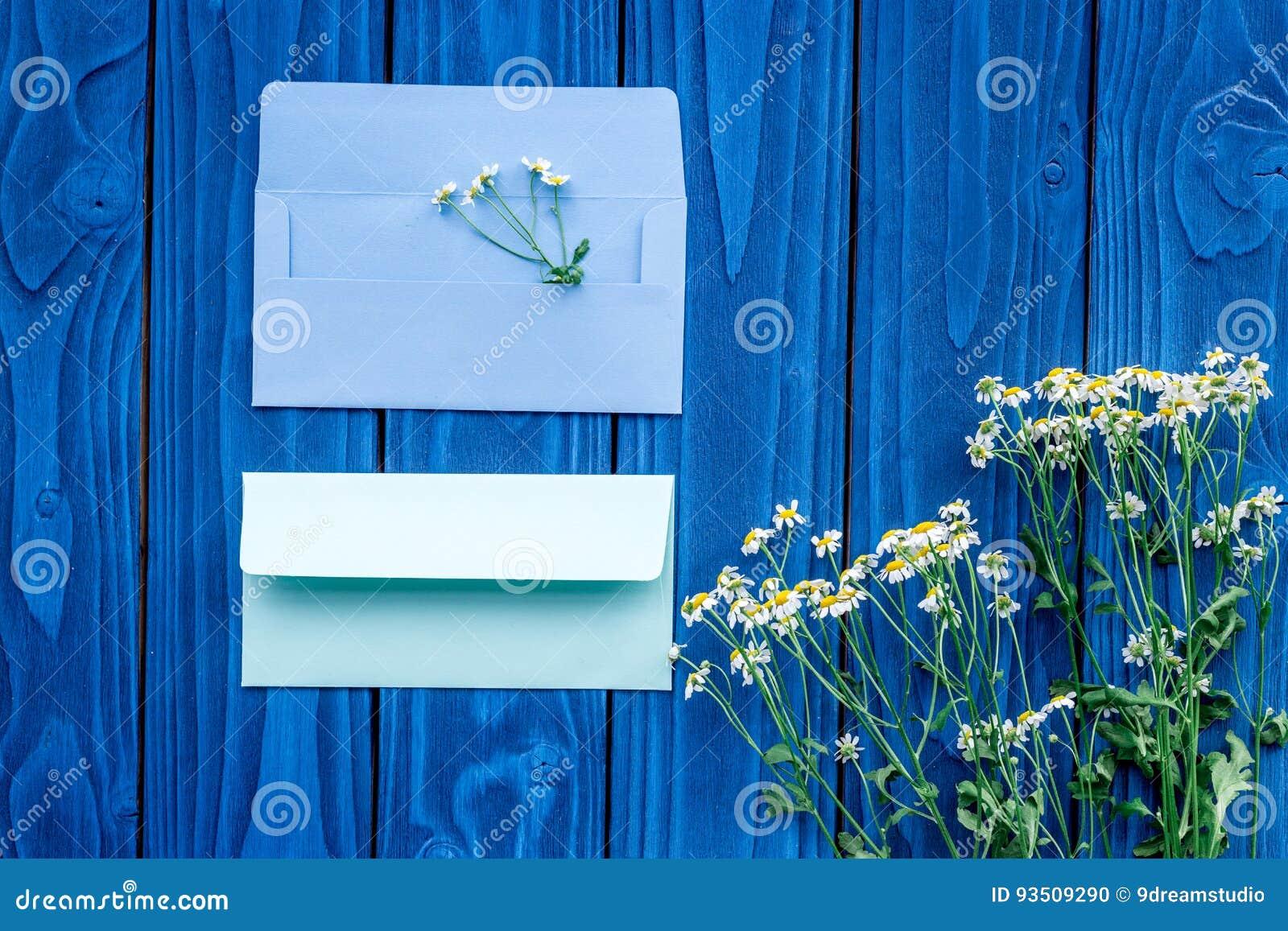 与春黄菊和明信片信封的花卉构成在蓝色木背景舱内甲板放置大模型