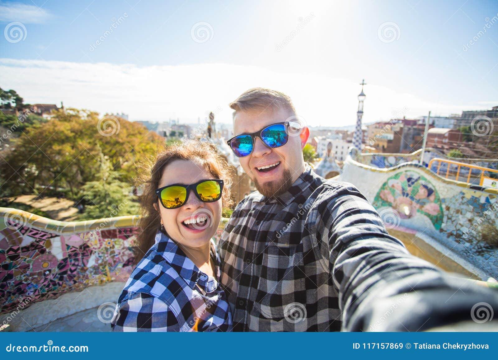 与智能手机的旅行夫妇愉快的制造的selfie画象在公园Guell,巴塞罗那,西班牙 美丽的夫妇年轻人