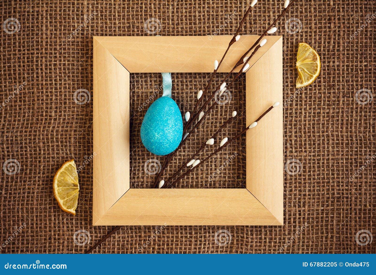 与木制框架、杨柳、鸡蛋和柠檬的复活节背景