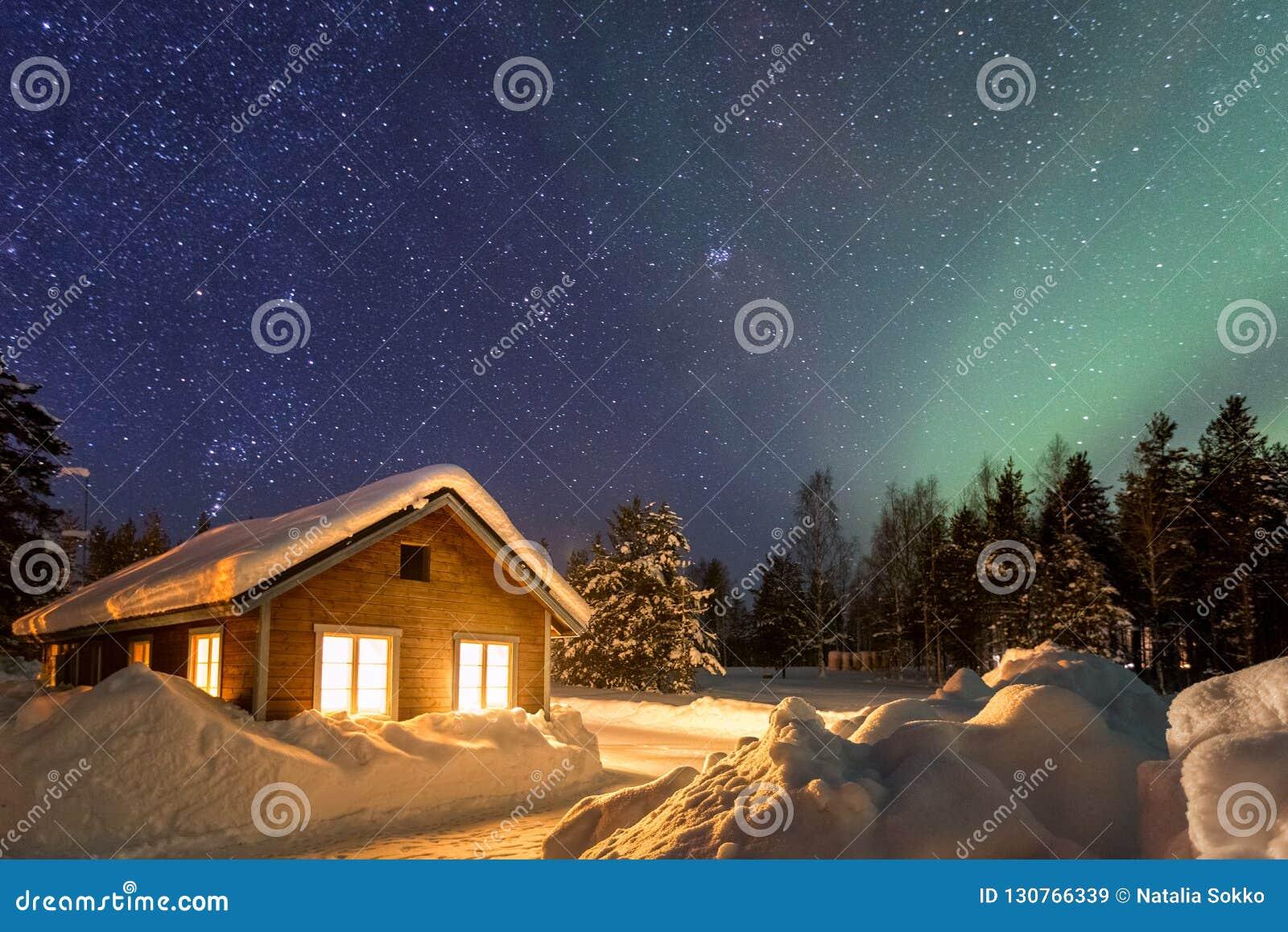 与木房子的冬天风景在美丽的满天星斗的天空下