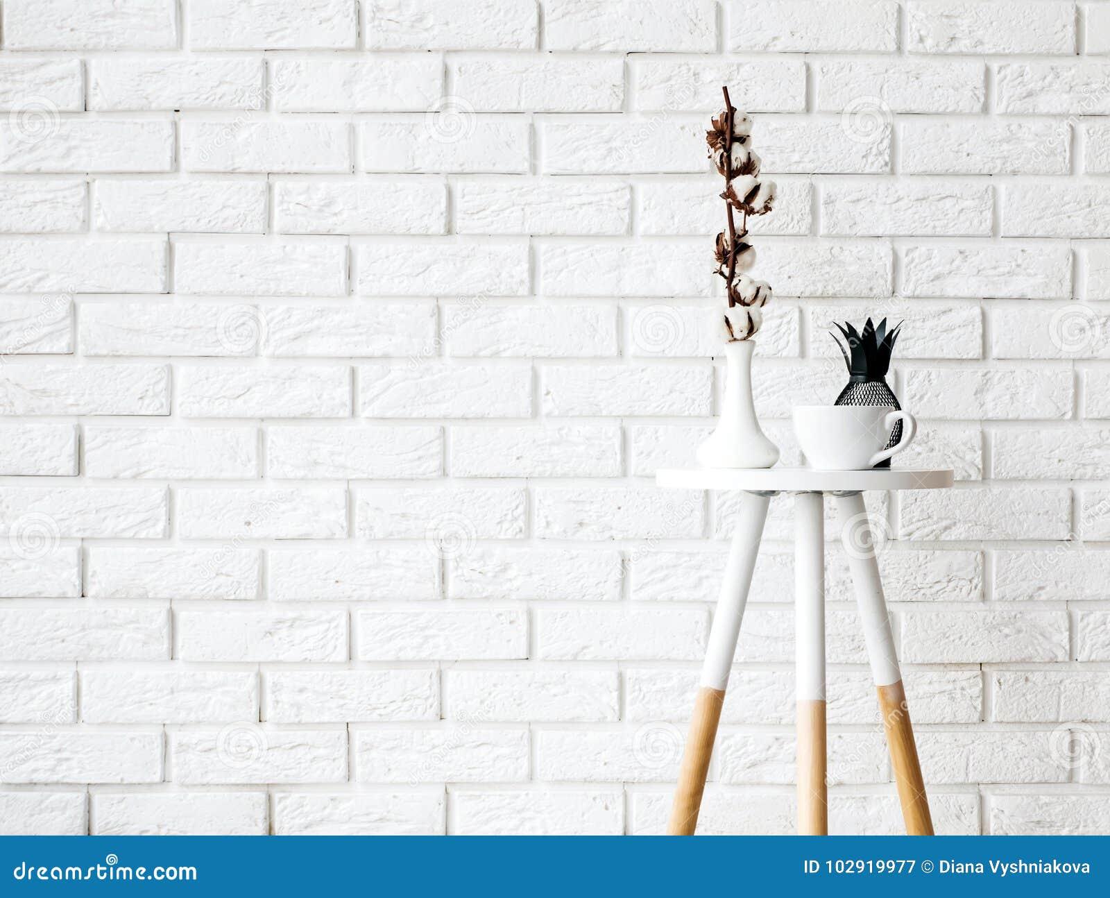与杯子和装饰的小咖啡桌在白色砖墙ba