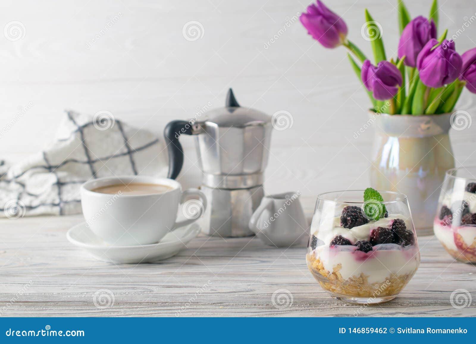 与格兰诺拉麦片、酸奶、咖啡和紫色郁金香花束的新鲜和健康早餐