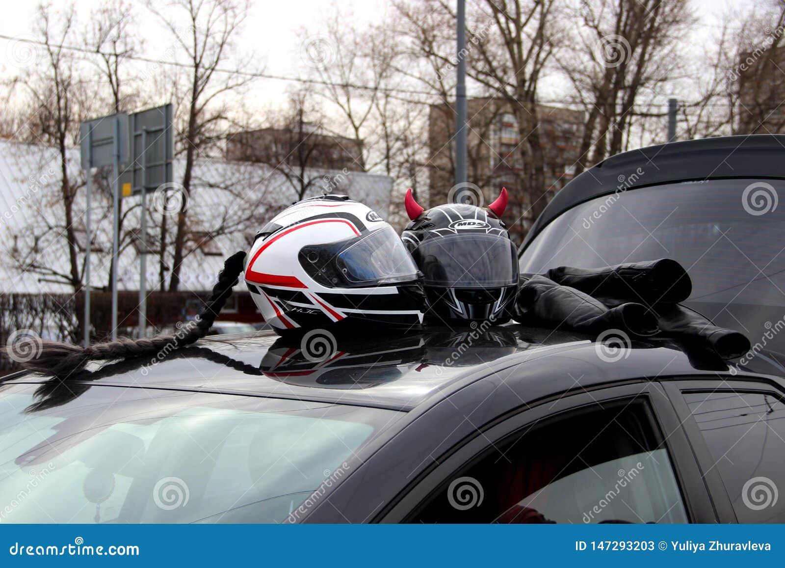 与桃红色垫铁和黑结辨的头发的两件摩托车盔甲在汽车的屋顶 注意摩托车季节的开头