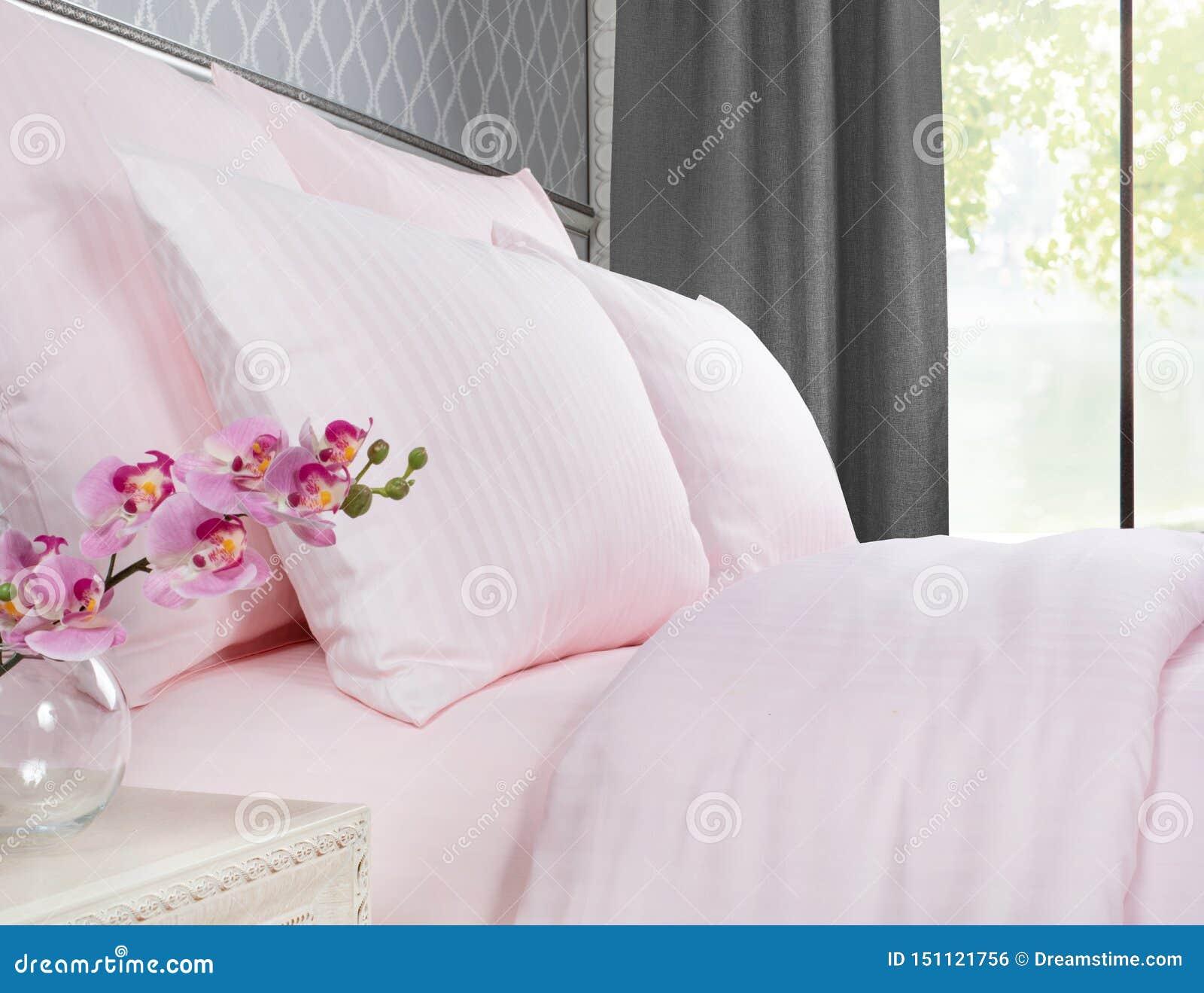 与桃红色床单的床反对与灰色帷幕的一个窗口