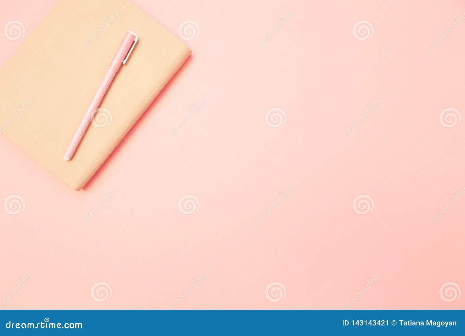 与桃红色笔的米黄日志在淡色千福年的桃红色纸背景 教育的概念,写博克 顶视图 平的位置