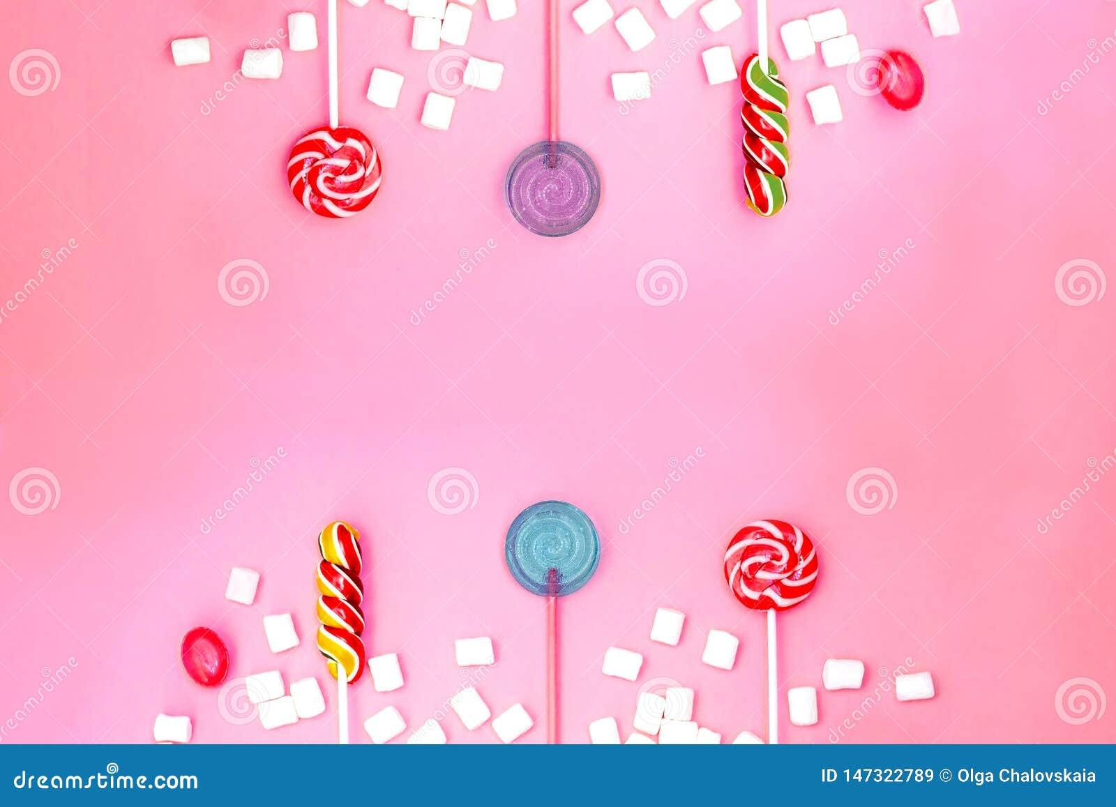 与棒棒糖和蛋白软糖框架的平的被放置的文本的构成和空间在桃红色背景