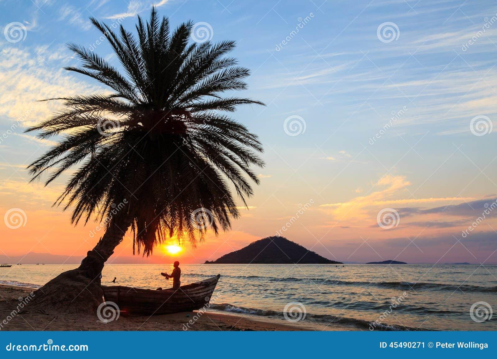 与棕榈树和小船的日落在海滩
