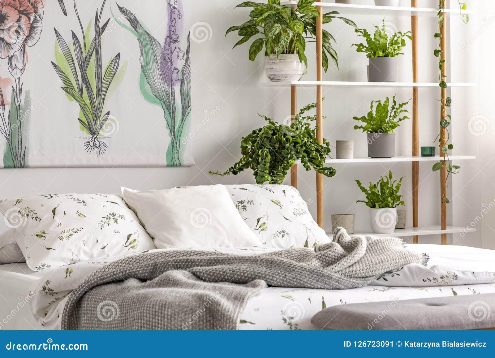与植物的都市密林卧室内部在床旁边的罐的在白色颜色有机棉花亚麻布穿戴了与绿色印刷品的 再