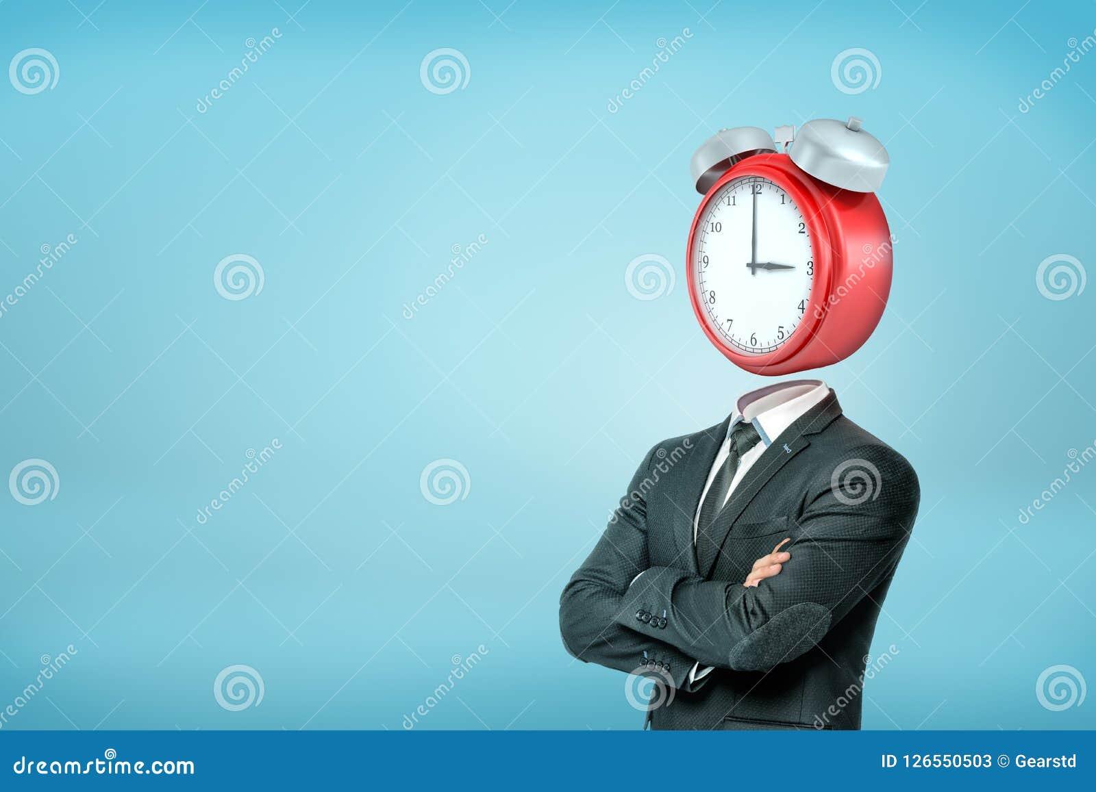 与横渡的胳膊的一个商人在与一个大红色闹钟的半轮站立而不是他的头