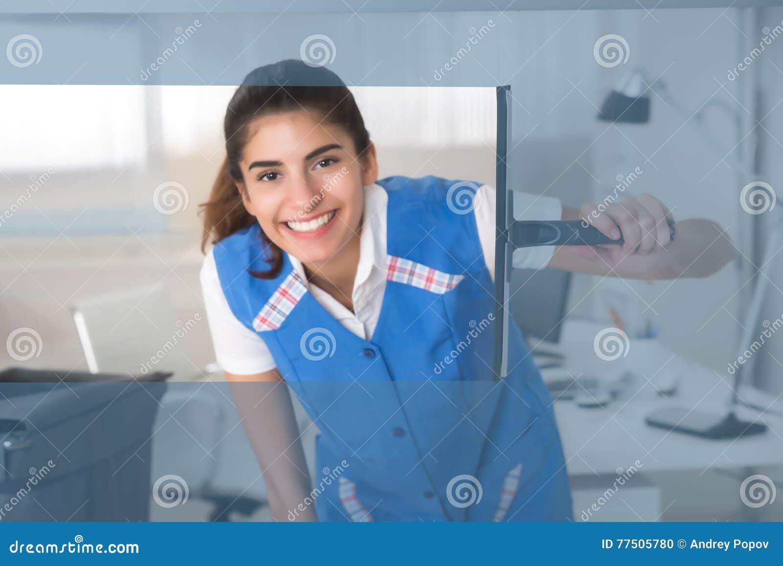 与橡皮刮板的微笑的女工清洗的玻璃窗