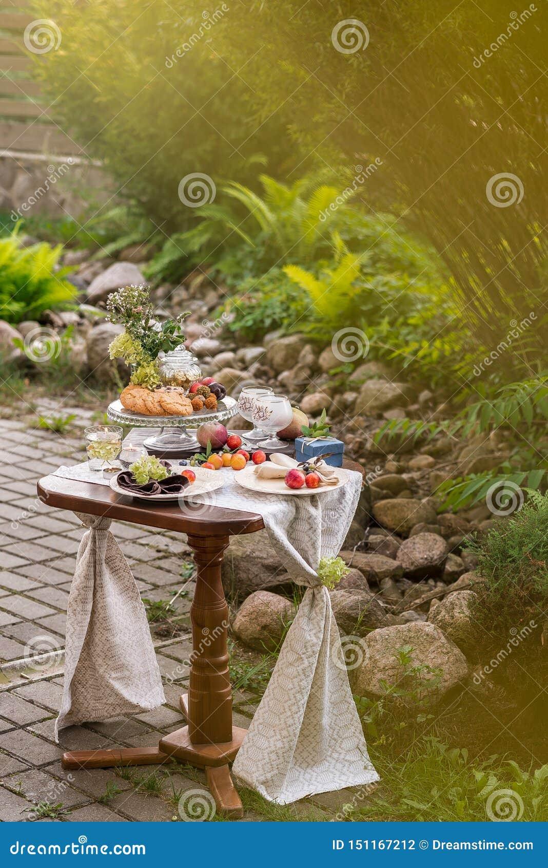 与欢乐款待的表和桌布在夏天庭院里