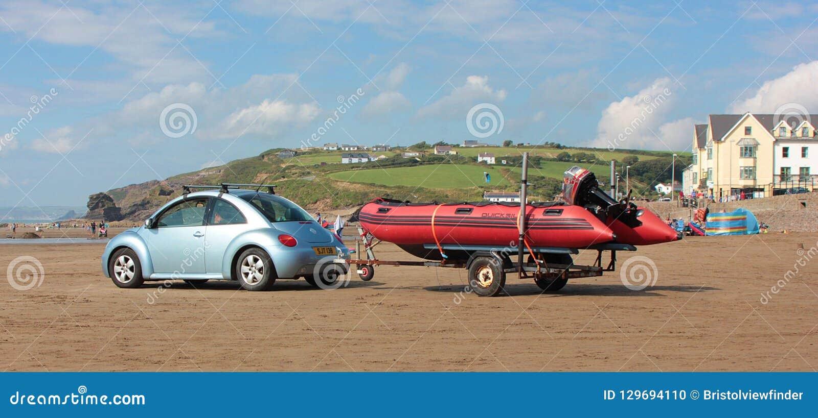 与汽车和充气救生艇拖车2018年8月的海滩场面