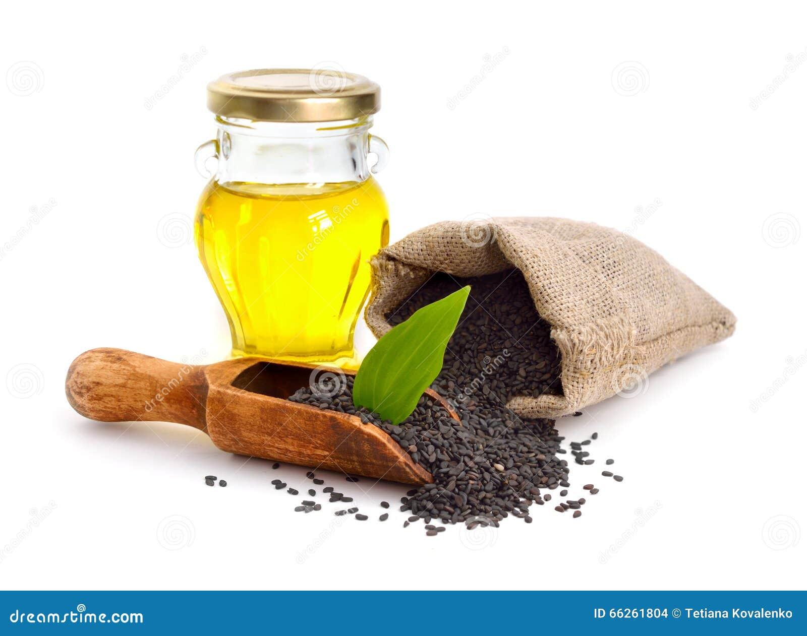 与油的黑芝麻籽 背景查出的白色