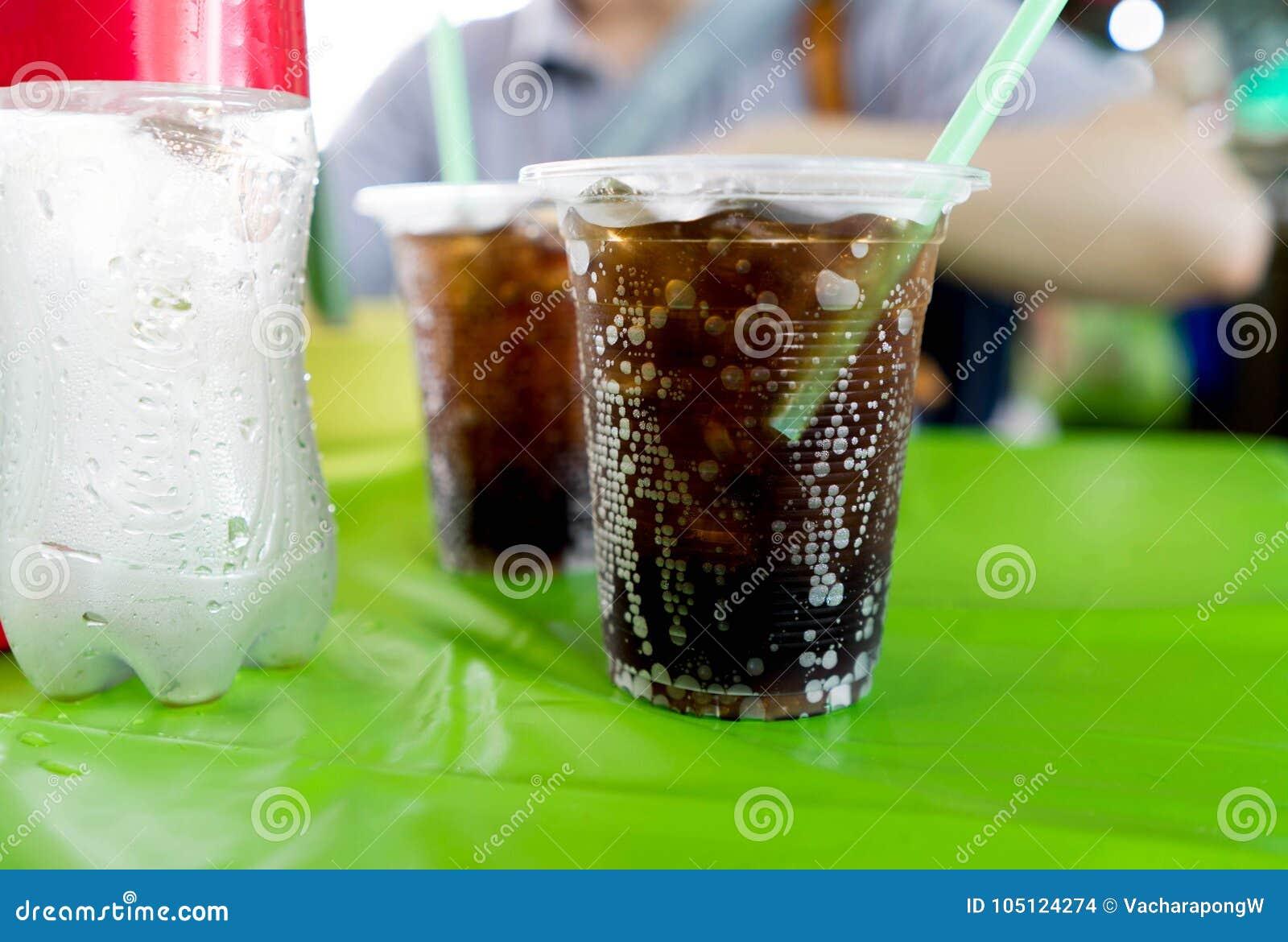 与泡影的黑闪耀的可乐水在有stro的塑料杯子