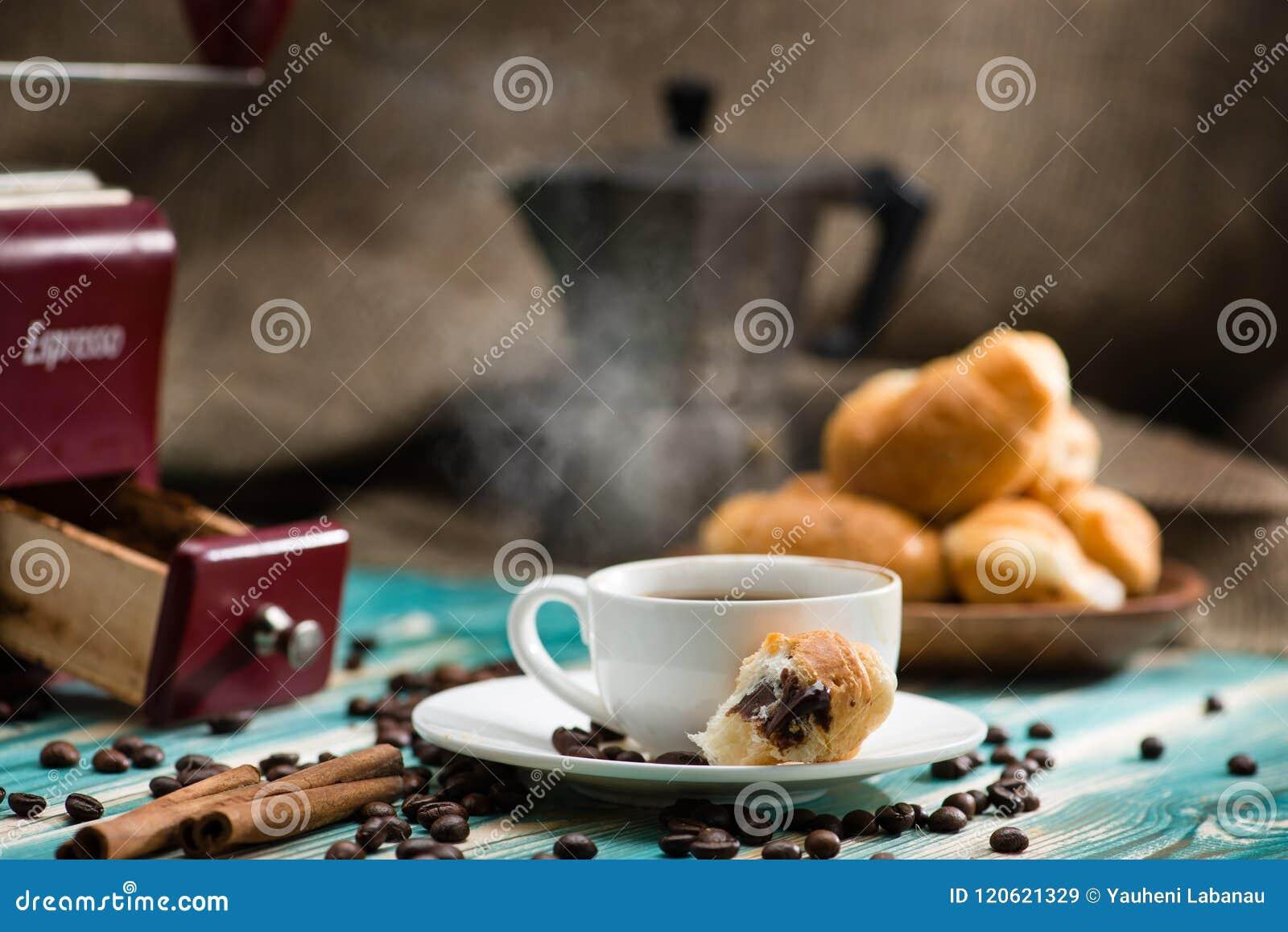 与浓咖啡杯子的早餐热的咖啡和新月形面包在向求爱
