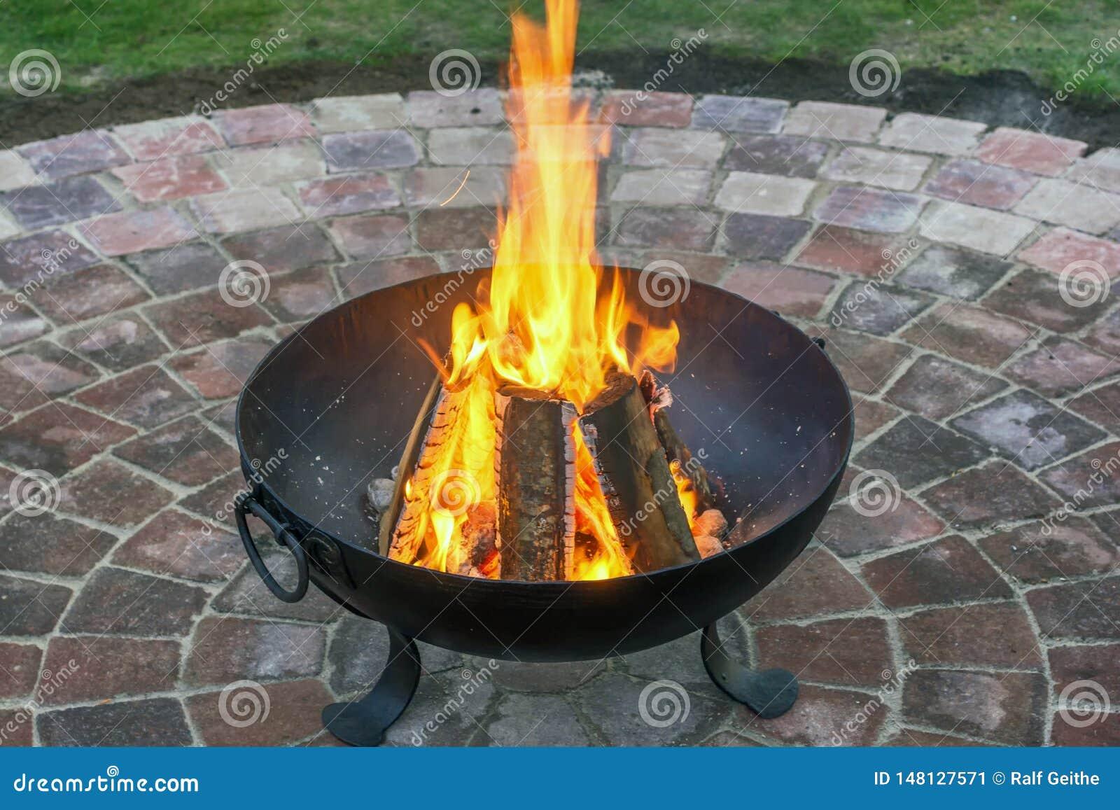 与温暖的火的伪造的火篮子在美好的铺路石圈子在庭院里