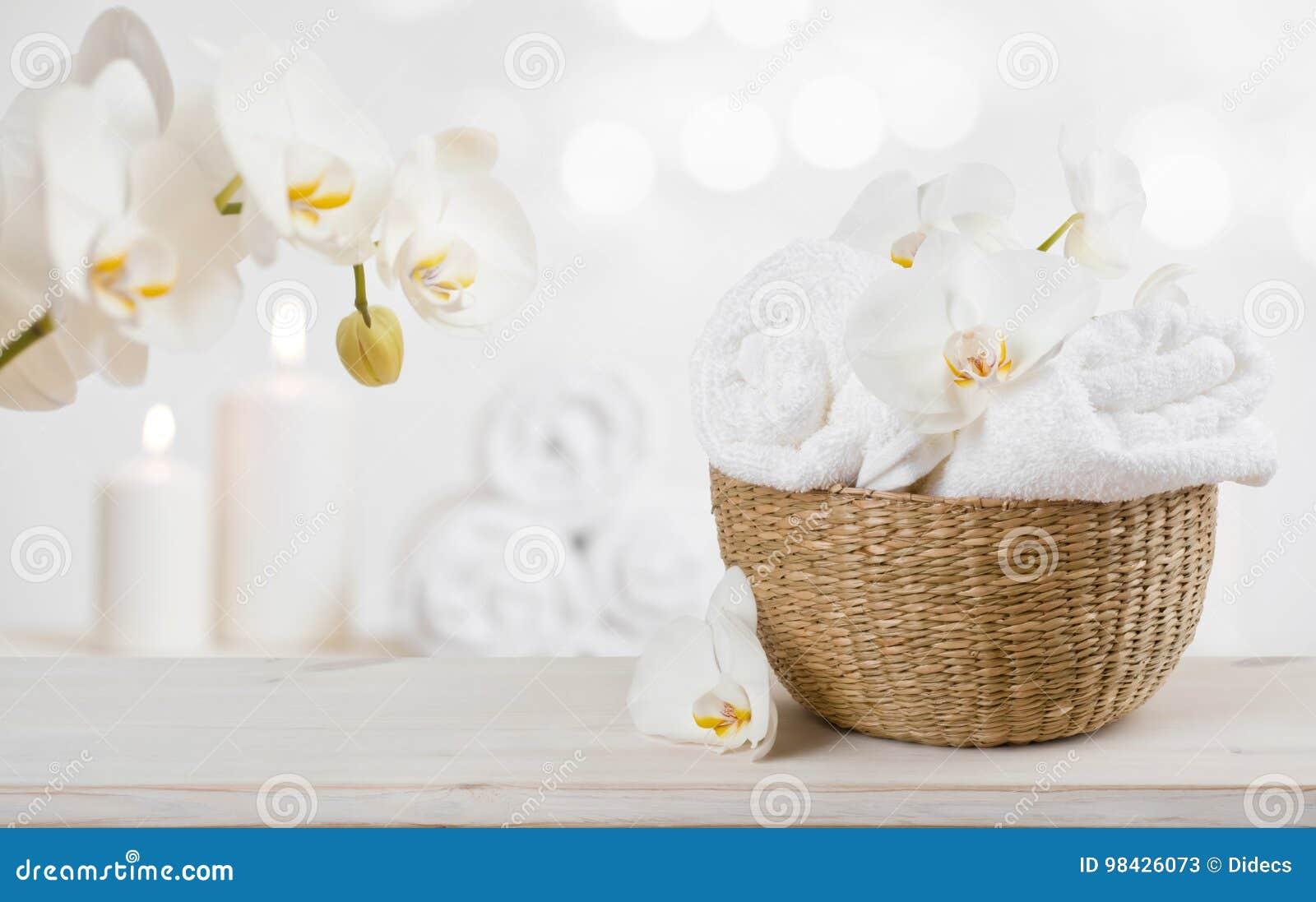 与温泉毛巾的柳条筐在抽象背景的桌上