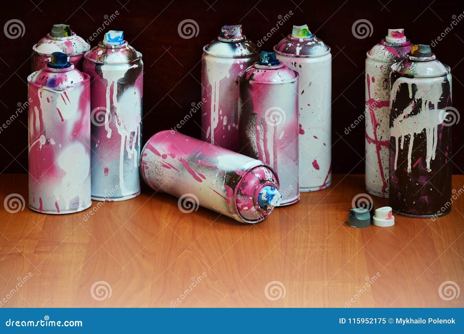 与湿剂油漆说谎在艺术家` s g的被对待的木表面上的很大数量使用的五颜六色的喷壶的静物画