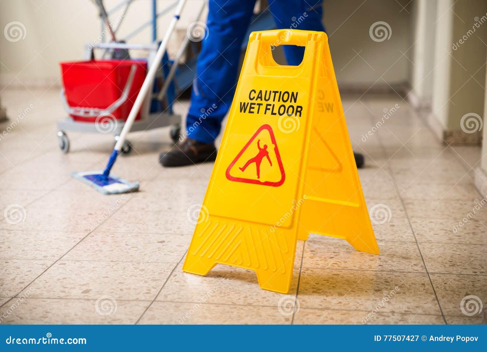 与湿地板小心标志的工作者擦的地板