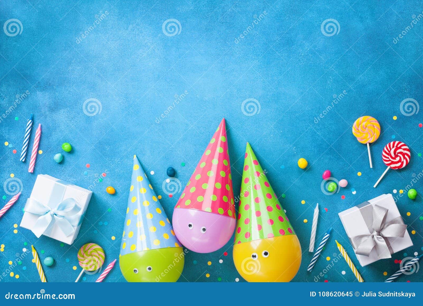 与滑稽的气球的生日背景在盖帽、礼物、五彩纸屑、糖果和蜡烛 平的位置 看板卡复制问候空间